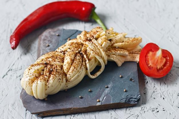 Käse mit gewürzen auf einem steinstand. suluguni-käse, tomaten, pfeffer
