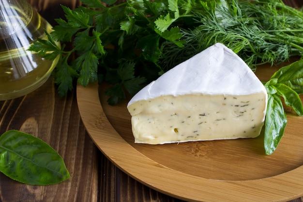 Käse mit kräutern auf dem holzschneidebrett