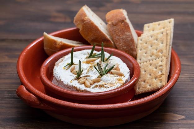 Käse mit kräutern, nüssen und honig in keramikschale Premium Fotos