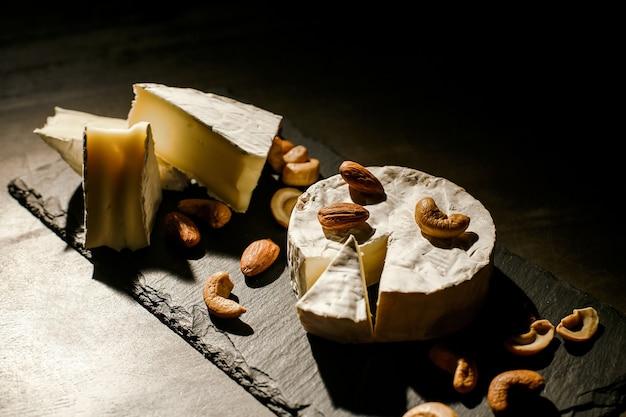 Käse mit nüssen auf dunklem hintergrund