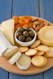 Käse mit oliven, trockenen früchten und keksen auf tablett