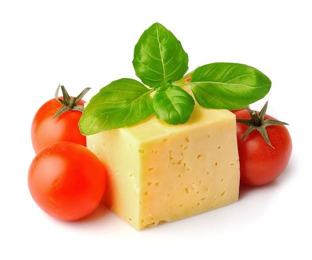 Käse mit tomaten und basilikumblättern isoliert
