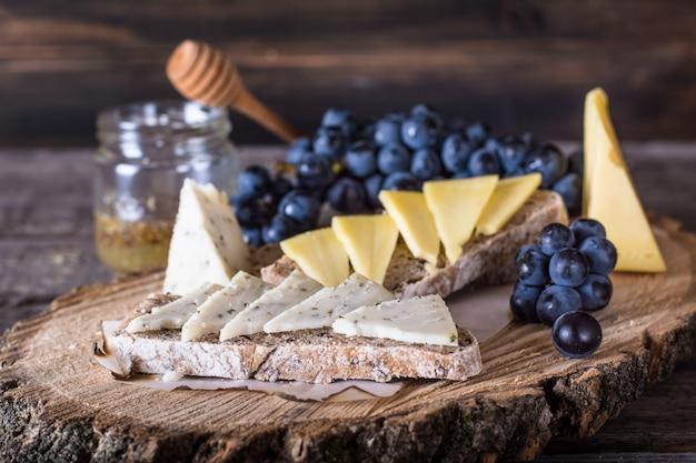 Käse mit trauben, brot, honig. ziegenkäse.bruschetta stillleben mit lebensmitteln. frühstück con