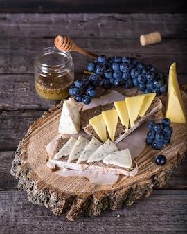 Käse mit trauben, brot, honig. ziegenkäse, kräuter. vorspeise. bruschetta mit käse