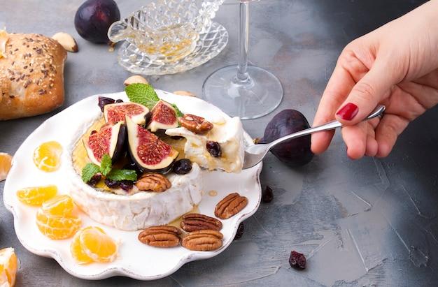 Käse mit weißem schimmel und feigen, honig und nüssen. herbst süßigkeiten und obst und wein. leckeres essen zum abendessen. ansicht von oben.