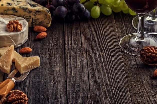 Käse, nüsse, trauben und rotwein auf holztisch