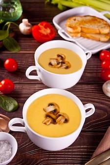 Käse- oder zwiebelcremesuppe mit toastbrot in weißen schalen