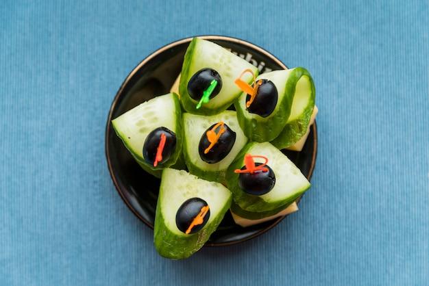 Käse, oliven und gurken auf plastikspieß auf untertasse