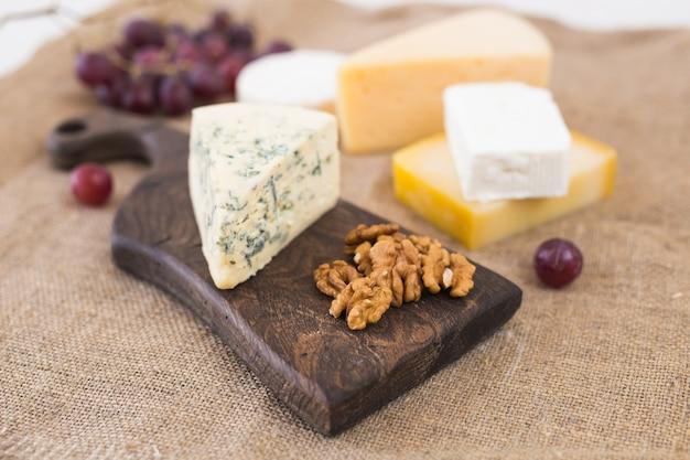 Käse-party-tisch, perfekte vorspeise für den urlaub mit nuss auf rustikalem holzbrett.