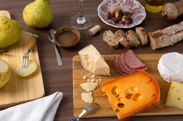 Käse, schinken, birnen und brot über hölzernem hintergrund