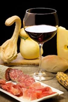 Käse, schinken und wein mit herbstlichen dekorationen