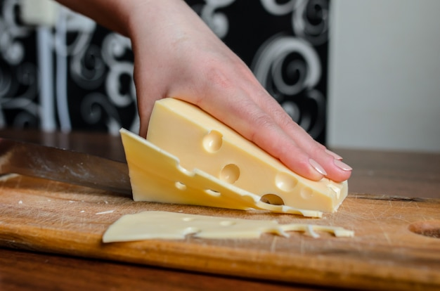 Käse schneiden auf einem holzbrett.