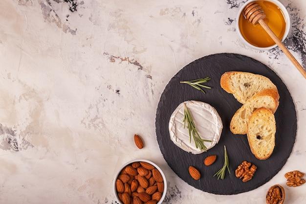 Käse serviert auf einem teller mit baguette, verschiedenen nüssen und honig