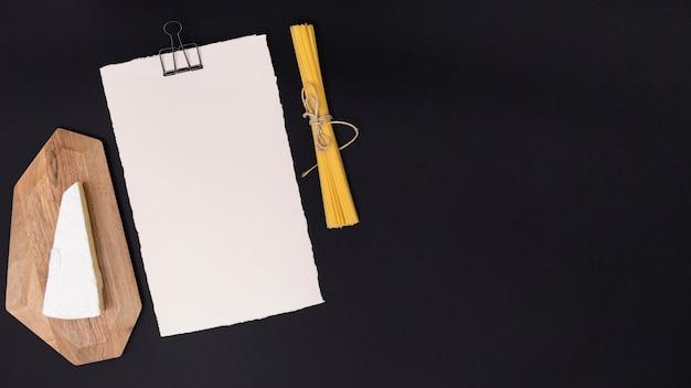 Käse; spaghettiteigwaren und weißes leeres papier auf schwarzem hintergrund