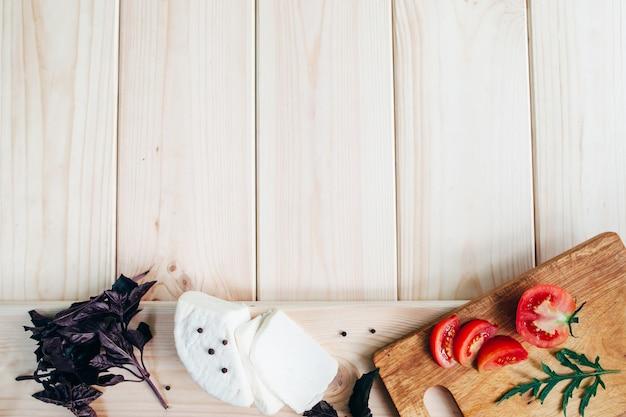 Käse-tomaten-basilikum auf hellem holzschreibtisch