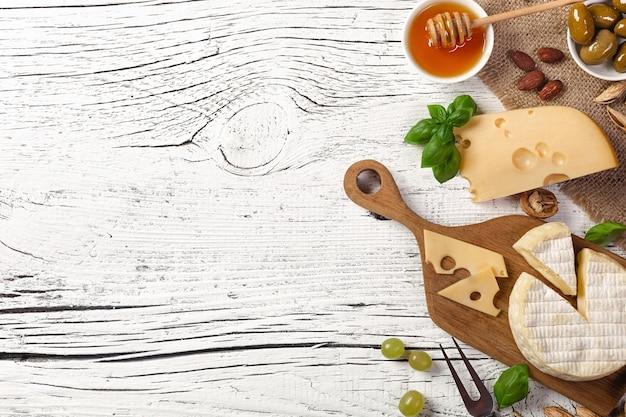 Käse, traube, honig und nüsse auf weißem holztisch. ansicht von oben.