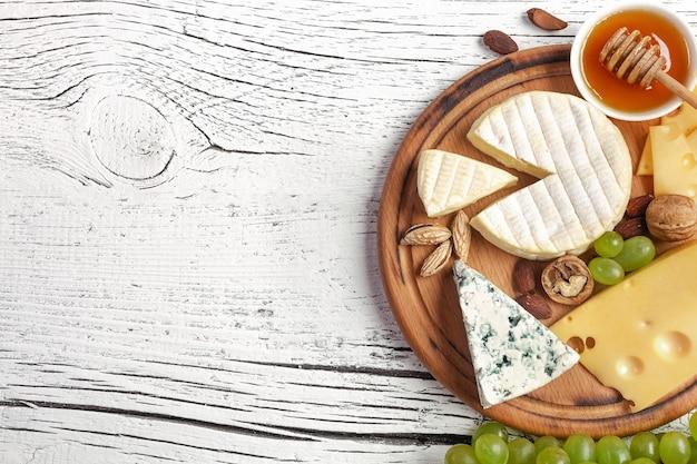 Käse, trauben, honig und nüsse auf schneidebrett und weißem holztisch. ansicht von oben.