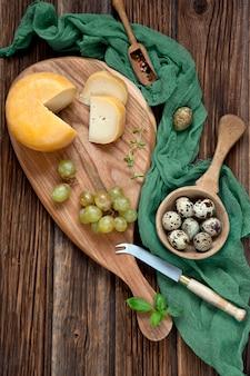 Käse, trauben und wachteleier auf rustikalem hölzernem hintergrund.