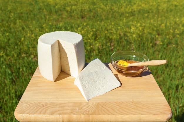 Käse und eine tasse mit honig auf dem hintergrund einer grünen wiese