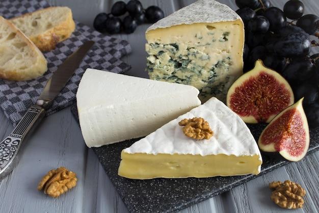 Käse und früchte auf dem grauen hölzernen hintergrund