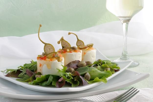 Käse und kapern süß-sauer-sauce und pistazien in den grünen blättern mit einem glas weißwein