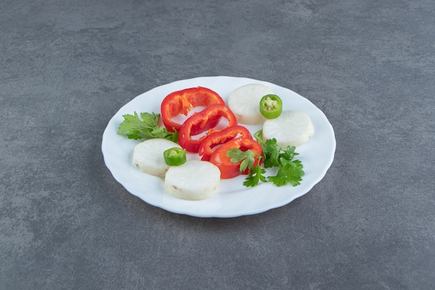 Käse- und pfefferscheiben auf weißem teller.