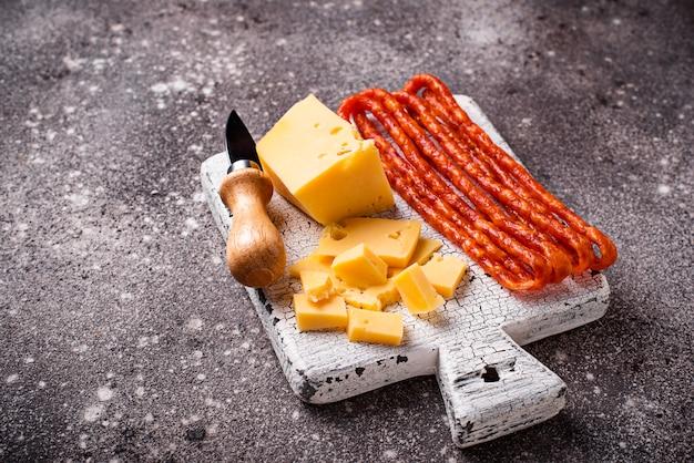 Käse- und salamiwurst auf hölzernem brett