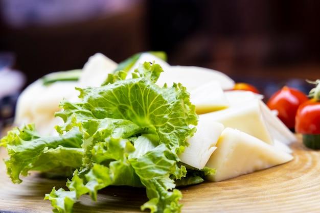 Käse und salat auf holzteller