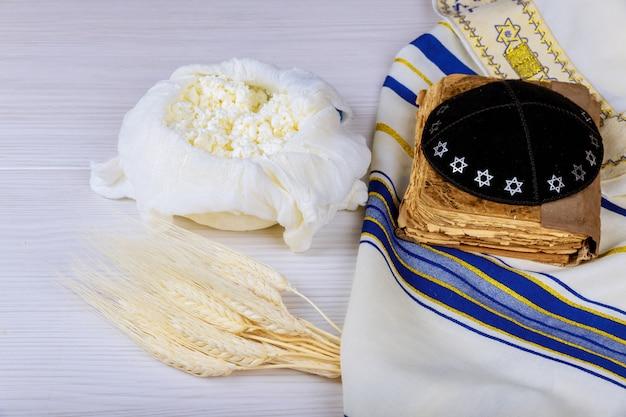 Käse und shofar, milchprodukte auf hölzernem weißem hintergrund