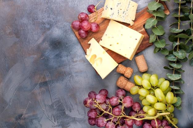 Käse und trauben auf einem schwarzen grauen konkreten hintergrund