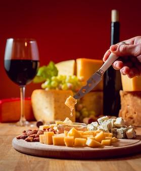 Käse und wein auf einem dunklen tisch.