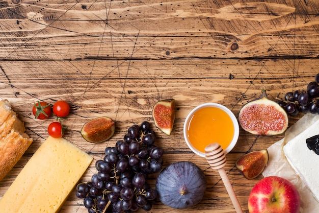 Käse, wein, stangenbrottraubenfeigenhonig und snäcke auf die rustikale holztischoberseite mit kopienraum.