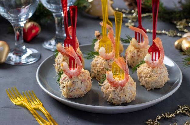 Käsebällchen mit krabbenstangen und garnelen - festlicher snack für weihnachten und neujahr auf grau. nahansicht