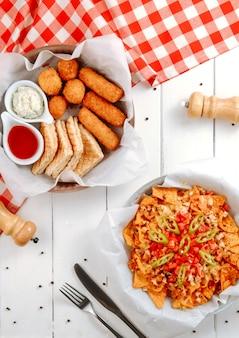 Käsebällchen sticks und sandwiches mit nachos auf dem tisch