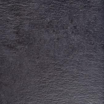 Käsebasaltsteinbretthintergrund, käsestand, schieferplatte. schwarzer steinschiefer, abschluss oben.