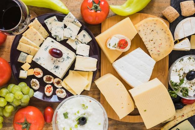 Käseblöcke und -scheiben mit tomaten, trauben und grünem paprikapfeffer auf tabelle