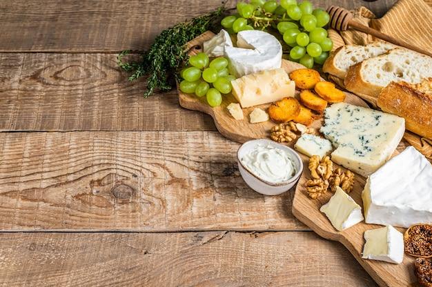 Käsebrett. brie, camembert, roquefort, parmesan und blauschimmelkäse mit trauben, feigen, brot und nüssen auf holzbrett.