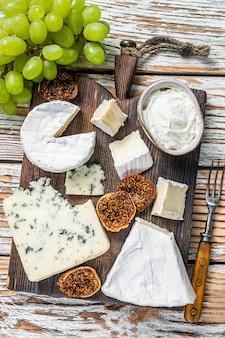 Käsebrett mit brie, camembert, gorgonzola und blauschimmelkäse. weißer hölzerner hintergrund. draufsicht.