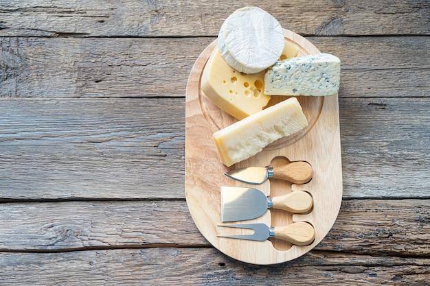 Käsebrett mit camembert-käse, parmesan-käse, maasdam-käse. ansicht von oben, kopienraum.