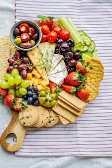 Käsebrett mit frischen früchten und crackern