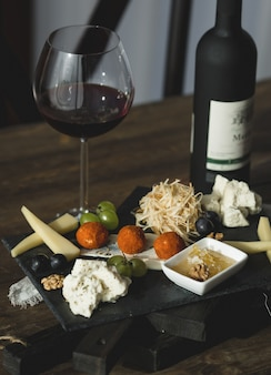 Käsebrett mit käsebällchen und einem glas wein