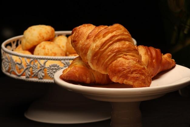 Käsebrot und butterhörnchen auf schöner platte zum köstlichen frühstück