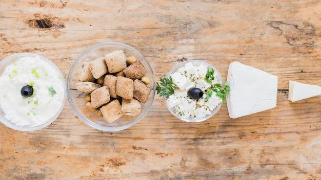 Käsedip, gebäck und käsewürfel auf hölzernem schreibtisch