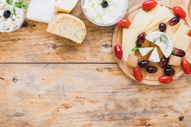 Käsedip und blöcke mit trauben und tomaten auf hölzernem schreibtisch