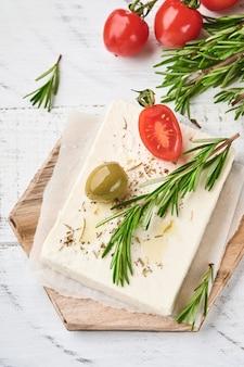 Käsefeta mit rosmarin, kräutern, kirschtomaten, oliven und olivenöl auf holzschneidebrett