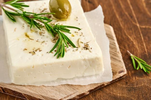 Käsefeta mit rosmarin, kräutern, oliven und olivenöl auf holzschneidebrett auf alter holzoberfläche