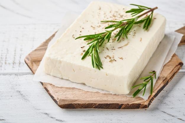 Käsefeta mit rosmarin, kräutern und olivenöl auf holzschneidebrett