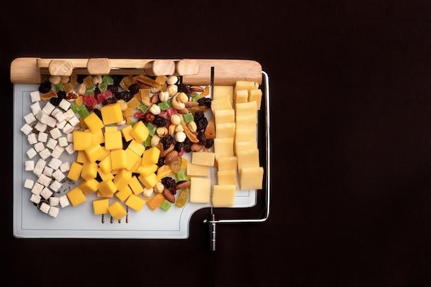 Käsegericht mit verschiedenen käsesorten und getrockneten früchten auf einem geschnittenen brett mit vorrichtungen zum schneiden