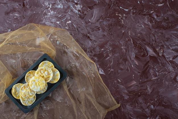 Käsekartoffelchips in einer holzplatte auf tüll, auf dem marmortisch.