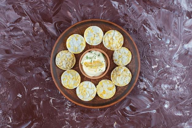 Käsekartoffelchips und joghurt in holzplatte, auf dem marmortisch.